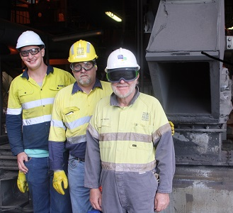 Three men standing in front of furnace
