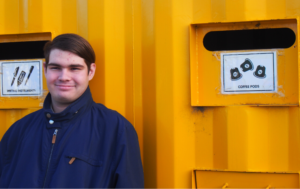James is standing in front of a large yellow recycling collection bin