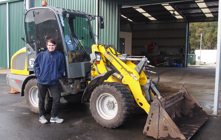 James is standing in front of a compact loader