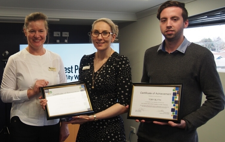 Three people are standing and holding two framed certificates