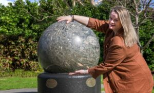 Liza is holding her arms around a giant revolving granite ball in the park at the City of Bunbury main administration building