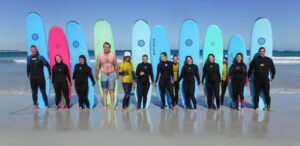 Alicia and a group of others stand in front of surfboards on a beach