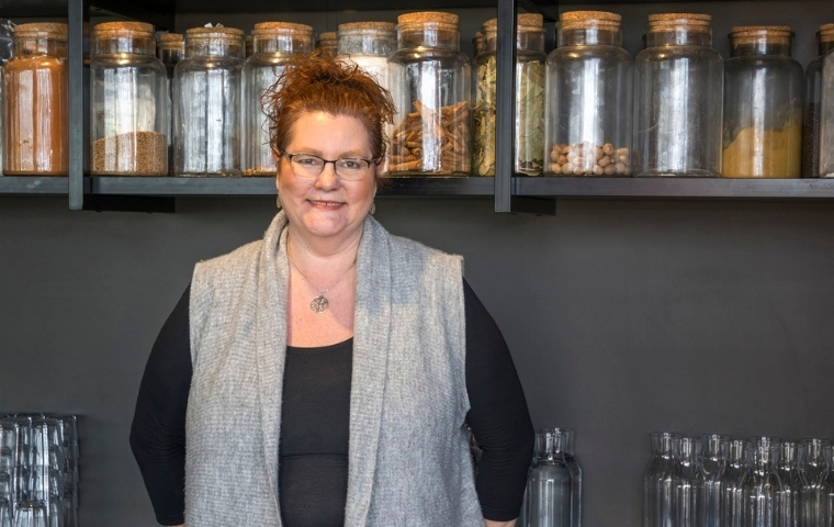 Jacqui stands facing the camera with her back to a wall of shelves with glass jars