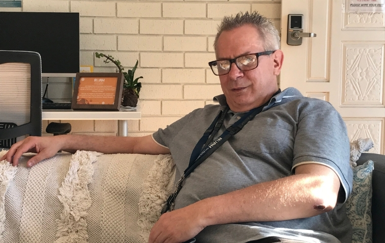 Nigel Tremain is sitting on a sofa and has his right arm extended along the back of the sofa