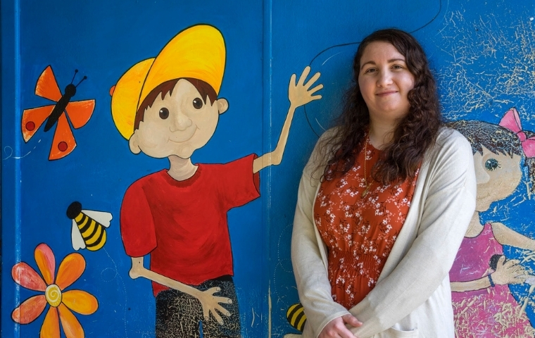 Lorelei Giorgi is standing with her back to a colourful wall mural featuring a young person wearing a red T-shirt and yellow cap