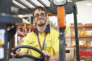 Cameron is sitting in a forklift and smiling at the camera