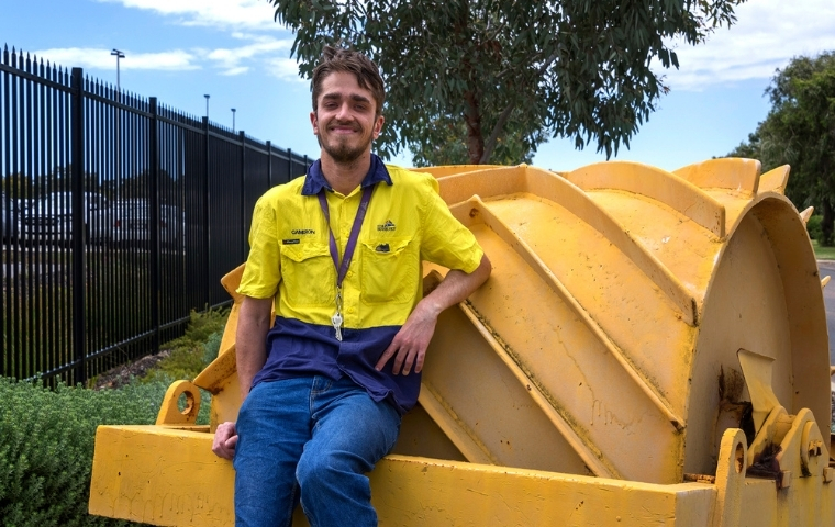 Cameron Payne is sitting of a piece of heavy machinery on display at the City of Bunbury