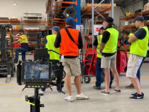 The film crew is watching as Cameron gets into his forklift