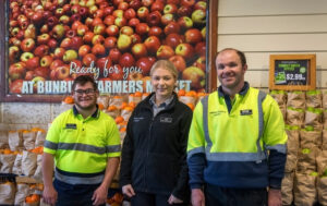Mitch, Jess and Ryan are standing at the Bunbury Farmers Market and are looking at the camera
