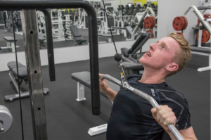 Pat is seated and is using a lateral pulldown machine at the gym