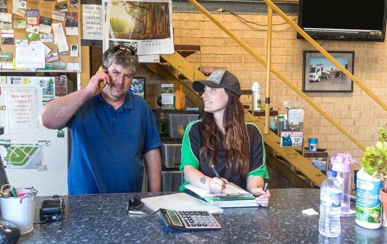 Ryan is standing with Karen at the front counter of Australind Landscaping Supplies. Ryan is holding the phone to his ear. Karen is looking at him