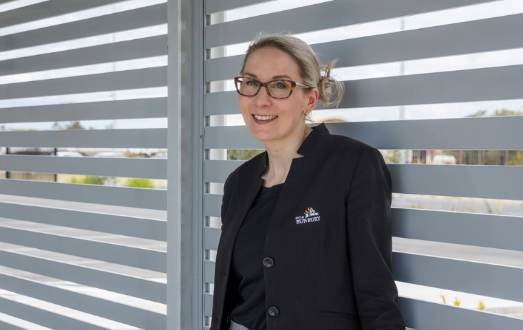 Tina Westrup is standing with her back against a slatted wall. She is wearing a black jacket and glasses and is looking at the camera