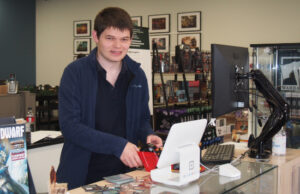 Cameron Black is standing behind the front counter of Beyond Games and Hobby