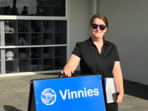Chenayah is standing at the front of Vinnies with her hand on a Vinnies sandwich board. She is dressed in black and is wearing dark sunglasses
