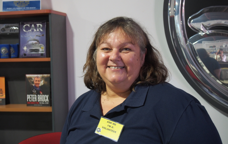 Cheryl is standing behind the counter of the Bunbury Geographe Motor Museum. She is smiling and looking at the camera