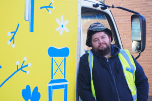 Heath is leaning against a Vinnies truck. The truck is painted yellow and Heath is wearing a yellow hi-vis vest