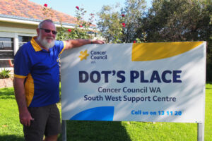 John is standing beside a sign for Dot's Place. He has one hand placed on top of the sign
