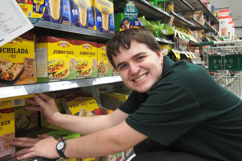 Smiling young man named Justin Gemmill is crouched in front of supermarket shelves