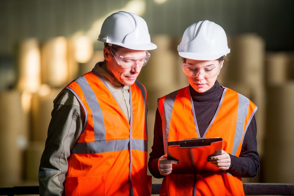 A male and female warehouse working wearing orange work vests and hardhats look at a clipboard.